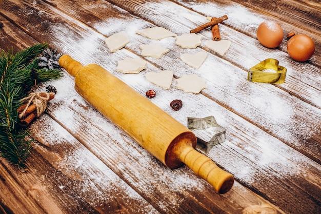Legen sie auf den holztisch mit nudelholz, teig, eiern und mehl zum kochen weihnachtsgebäck