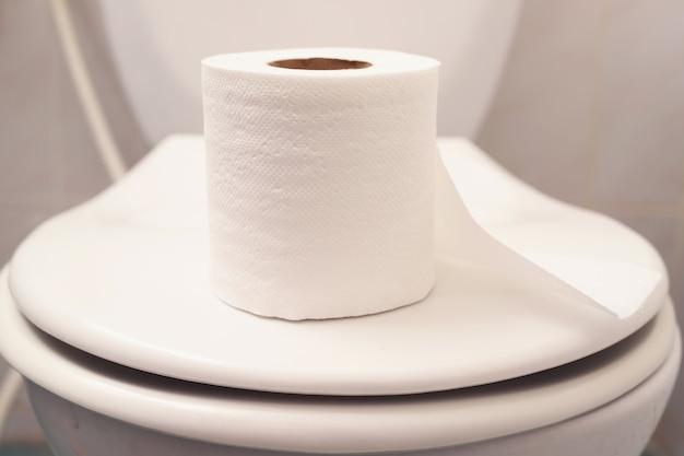 Legen sie das toilettenpapier zur verwendung auf den toilettendeckel.