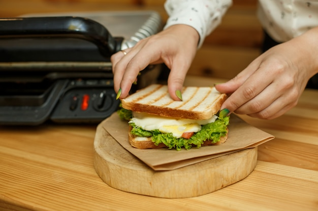 Legen sie den geschmolzenen käse in ein sandwich. kochen saftiges sandwich