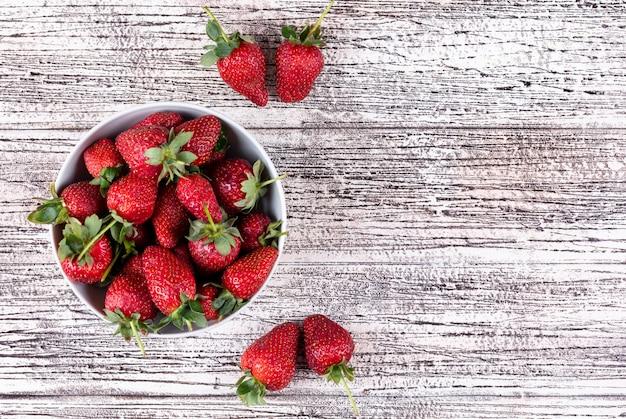 Legen sie die erdbeeren flach in eine schüssel und andere auf einen hellen holztisch
