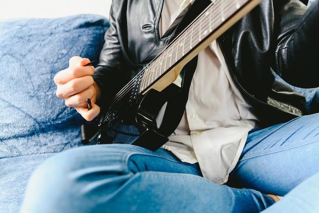 Legen sie die finger auf eine gitarre, um einige noten eines professionellen gitarristen zu spielen.