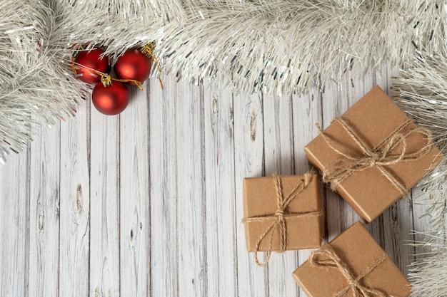 Legen sie drei geschenkboxen flach auf einen holztisch, der mit einer girlande und roten weihnachtskugeln für das neue jahr oder weihnachten verziert ist. post-, kurier- oder zustelldienstkonzept. kopieren sie platz