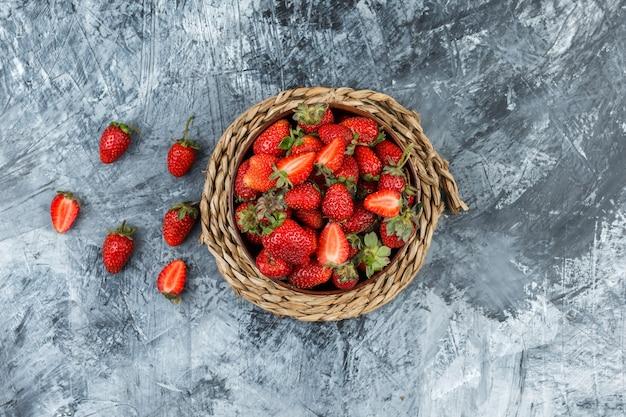 Legen sie flach eine schüssel erdbeeren auf ein tischset aus korbgeflecht auf eine dunkelblaue marmoroberfläche. horizontal