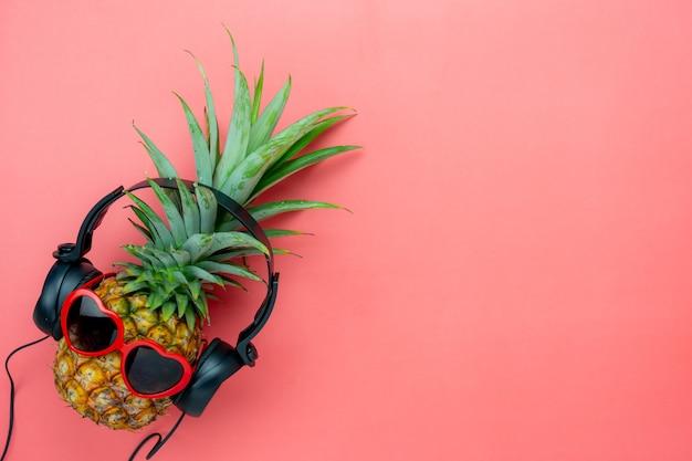 Legen sie flaches objekt das ananashörradio durch schwarzen kopfhörer für zeichen des jahreszeitlichen.