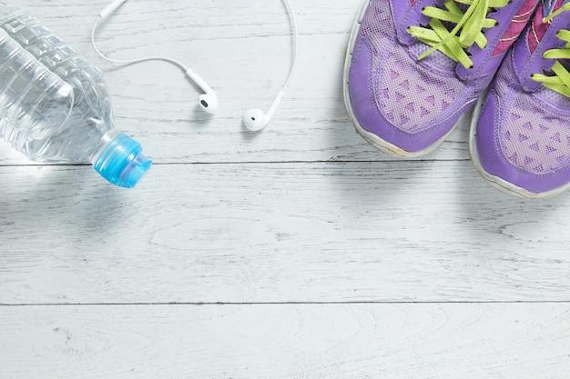 Legen sie purpurrote schuhe der sportebenen und trainingsausrüstungen auf weißem hölzernem hintergrund auf.
