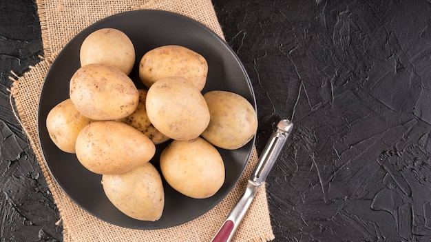 Legen sie rohe kartoffeln flach auf teller mit kopierraum