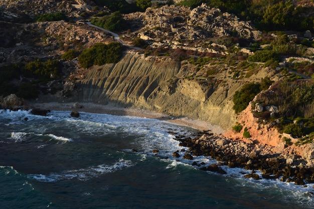 Lehmhänge, die durch verwitterung mit blauem ton und erosion auf dem seeweg in der bucht von fomm ir-rih, malta, gebildet wurden
