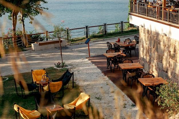 Lehnsesseltaschen und -tabellen auf dem gras in einem café