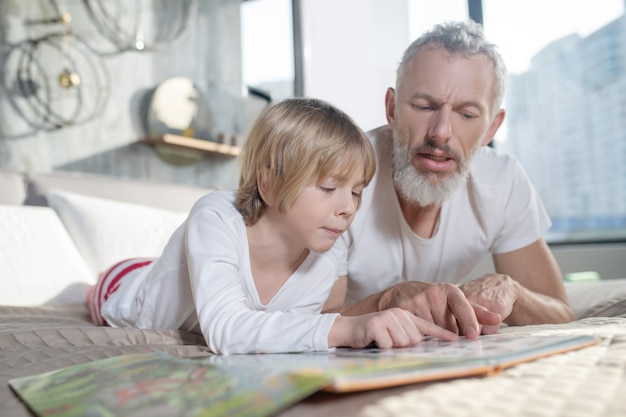 Lehren, lesen. ernsthafter grauhaariger vater, der dem kind das lesen beibringt, zu hause auf dem bett liegt und seine finger über das buch bewegt