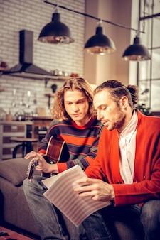 Lehrender student. bärtiger professioneller talentierter musiklehrer mit roter strickjacke, der seinen schüler unterrichtet