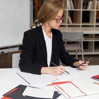 Lehrer am schreibtisch mit handy