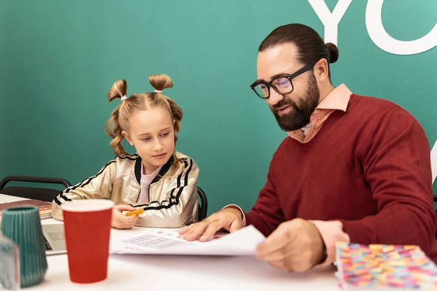 Lehrer bei der arbeit. dunkelhaariger bärtiger lächelnder lehrer, der einen braunen pullover trägt, der interessiert aussieht