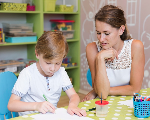 Lehrer beobachtet kind zeichnen