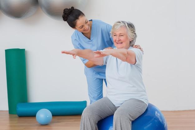 Lehrer, der ältere frau beim trainieren unterstützt