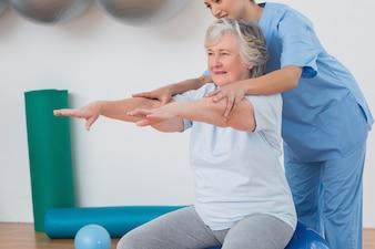Lehrer, der ältere frau unterstützt, um zu trainieren