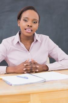 Lehrer, der am schreibtisch beim sprechen sitzt