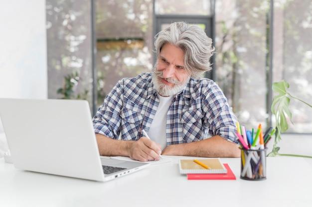 Lehrer, der am schreibtisch bleibt, der auf notizbuch schreibt und laptop betrachtet