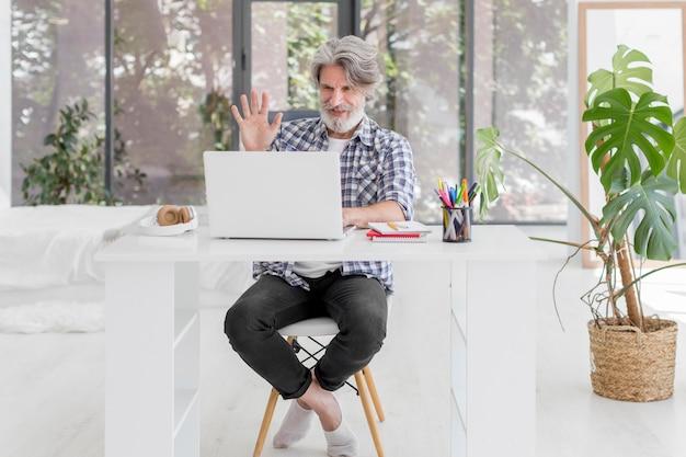 Lehrer, der am schreibtisch bleibt und am laptop winkt