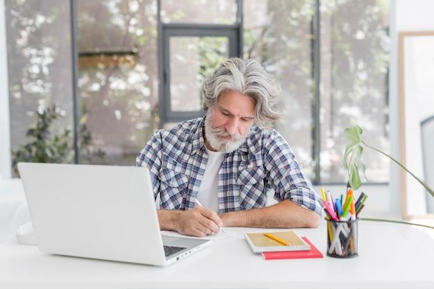 Lehrer, der am schreibtisch bleibt und auf notizbuch schreibt