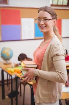 Lehrer, der an der kamera beim halten des stapels notizbücher lächelt