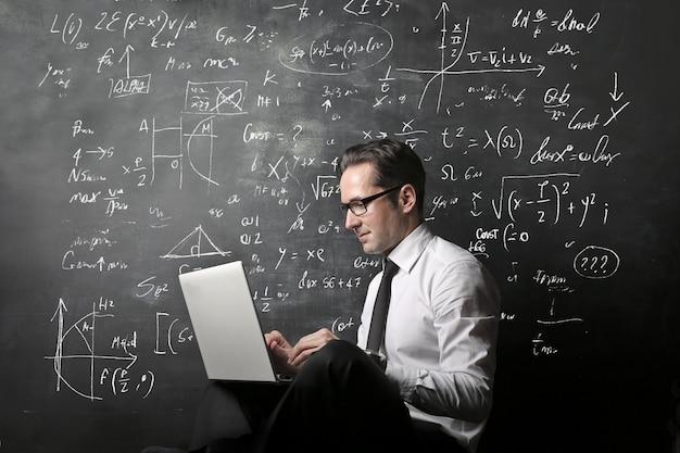 Lehrer, der an einem laptop arbeitet