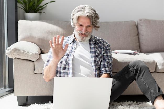 Lehrer, der auf dem boden bleibt und am laptop winkt