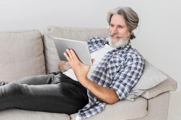 Lehrer, der auf der couch bleibt und tablette betrachtet