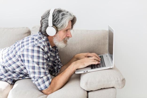 Lehrer, der auf der couch mit laptop bleibt