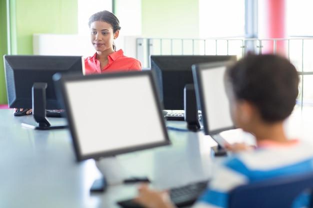 Lehrer, der computer im klassenzimmer benutzt