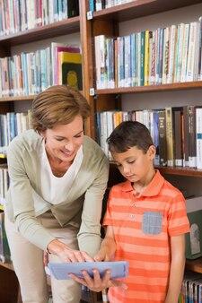 Lehrer, der dem schüler tablette auf bibliothek zeigt