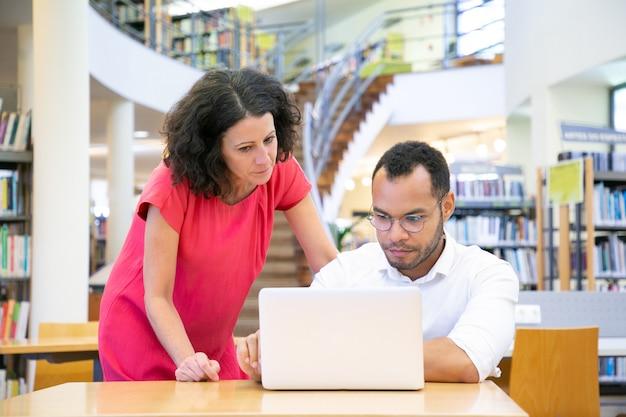 Lehrer, der dem studenten hilft, der an projekt arbeitet