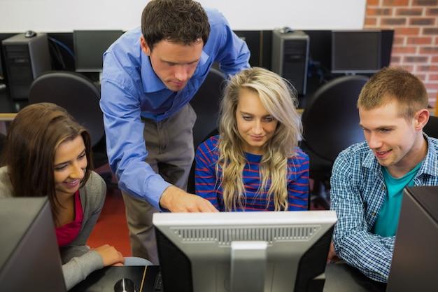 Lehrer, der den studenten etwas im bildschirm auf computerraum zeigt