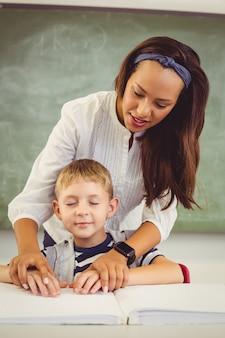 Lehrer, der einem jungen mit seinen hausaufgaben im klassenzimmer hilft