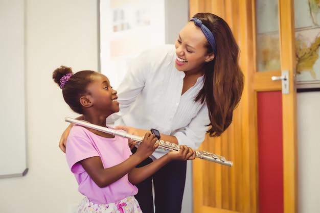 Lehrer, der einem mädchen hilft, eine flöte im klassenzimmer zu spielen