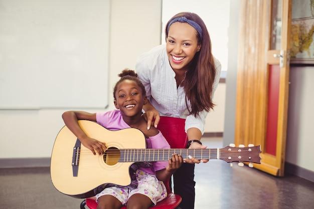 Lehrer, der einem mädchen hilft, eine gitarre im klassenzimmer zu spielen