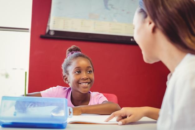 Lehrer, der einem mädchen mit ihren hausaufgaben im klassenzimmer hilft