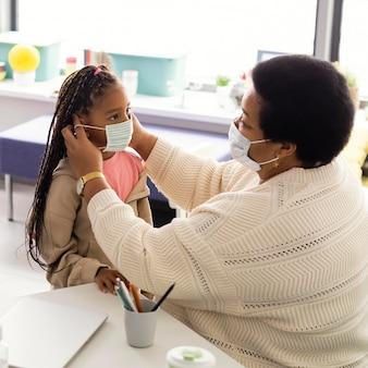 Lehrer, der einem schüler hilft, eine medizinische maske aufzusetzen