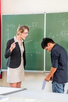Lehrer, der einen schüler in der schulklasse kritisiert