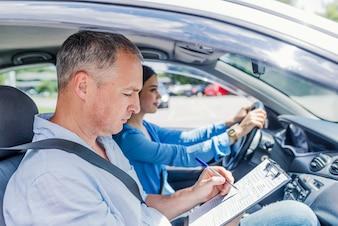 Lehrer der Fahrschule Prüfung beim Sitzen im Auto gebend.