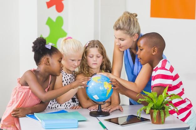 Lehrer, der globus mit kindern bespricht
