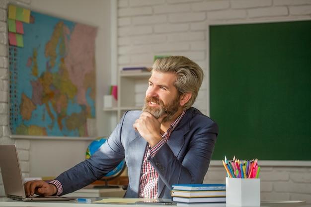 Lehrer, der im klassenzimmer an der grundschule lächelt. porträt des selbstbewussten männlichen lehrers im klassenzimmer. junge männliche lehrer mit laptop in der klasse sitzt am tisch die tafel im klassenzimmer.