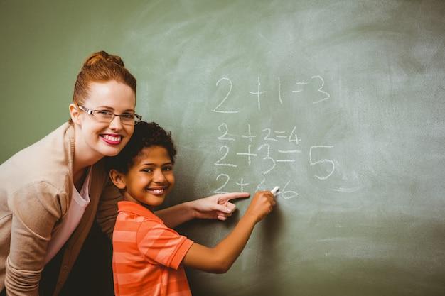 Lehrer, der jungen unterstützt, um auf tafel in klassenzimmer zu schreiben