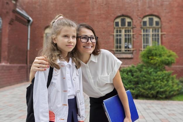 Lehrer, der kind nahe schulgebäude umarmt. zurück in die schule, beginn des unterrichts