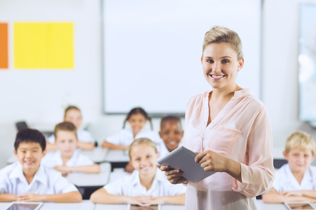 Lehrer, der kinder auf digitalem tablett unterrichtet