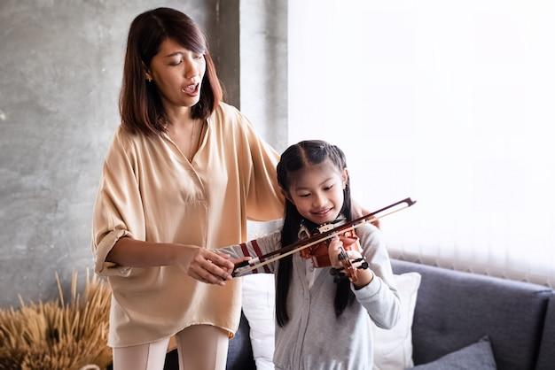 Lehrer, der kleines mädchen für das spielen der violine unterrichtet