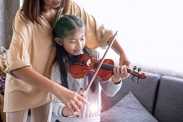 Lehrer, der kleines mädchen für das spielen der violinenmusikklasse, am studiomusikraum unterrichtet