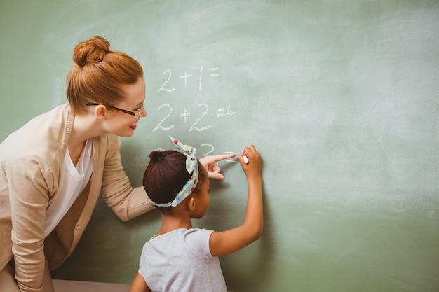 Lehrer, der mädchen unterstützt, um auf tafel in klassenzimmer zu schreiben