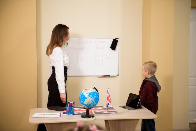 Lehrer, der männlichen schüler beim lesen am schreibtisch hilft.