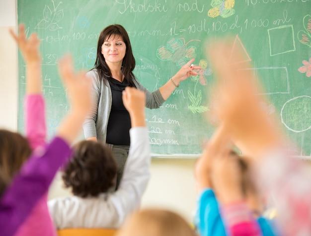 Lehrer, der mit kindern im schulklassenzimmer arbeitet