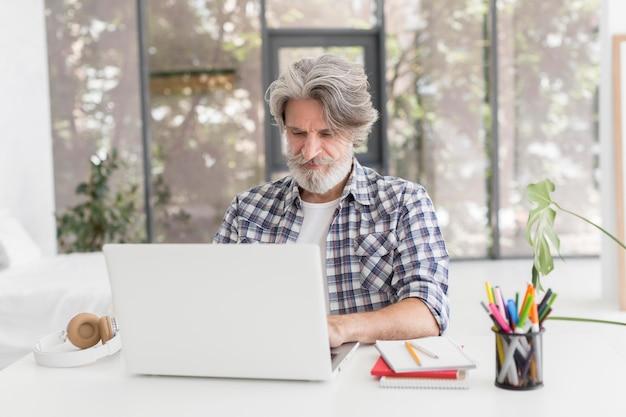 Lehrer, der mit laptop am schreibtisch bleibt